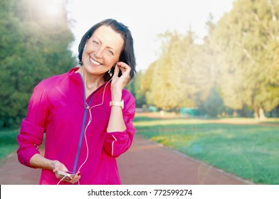 Mature woman listen music before or after jog in the park. Attractive looking mature woman keeping fit and healthy