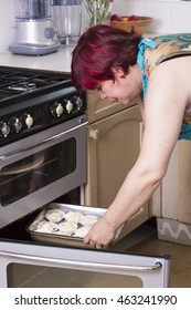Mature woman loading tray with pastry in oven at kitchen