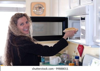 Mature woman loads food into the microwave oven