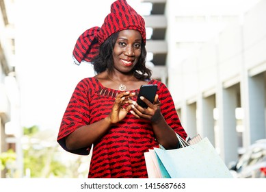 mature woman in loincloth standing outdoors looking at mobile phone while smiling with shopping bags.