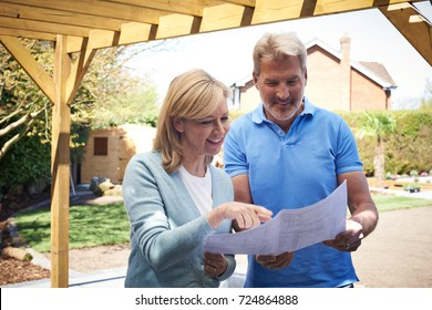 Mature Woman Looking At Design Plan With Landscape Gardener