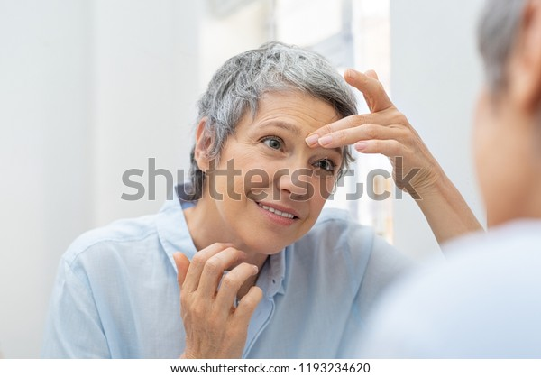 Mature woman looking her face and wrinkles in the bathroom mirror. Senior woman applying cosmetic lotion on skin between eyebrows while looking at mirror. Beautiful lady looking her face in morning.