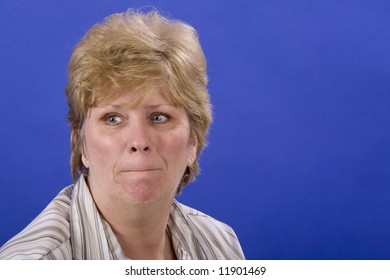 mature woman looking pensive on blue back ground