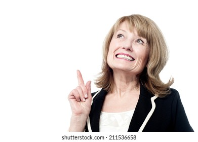 Mature woman looking and pointing up