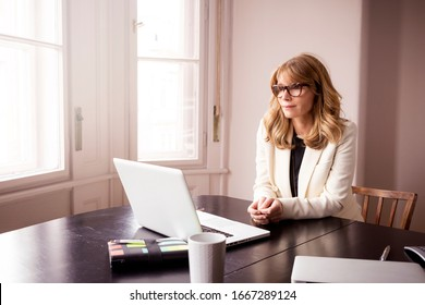 Mature woman looking thoughtfully while sitting behind her at home. Home office.
