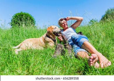 mature woman lying with a Labrador Retriever in the meadow at a hiking rest