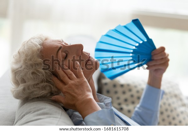 Mature woman lying on sofa in living room wave with hand fan suffer from heatstroke or hot summer weather, exhausted elderly female using waver saving from heat at home, hormone imbalance concept