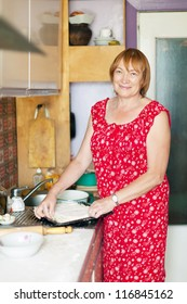 Mature woman makes pie with fillings in her kitchen