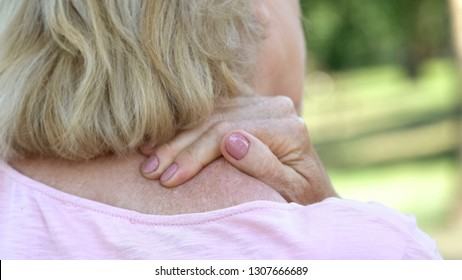 Mature woman massaging numb neck and shoulders, spine injury consequences