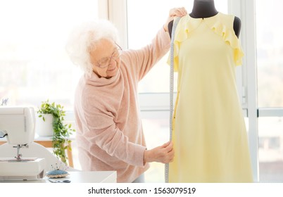 mature woman measuring dress on mannequin in atelier