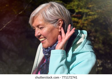 Mature woman in middle age with nice gray hair outdoor in nature portrait with sunlight
