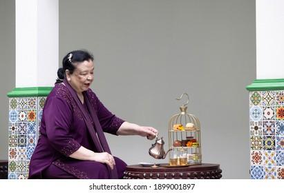 A mature woman of mixed Indo-Aryan-Asian races in purple Punjabi attire enjoying a setting of an afternoon tea.