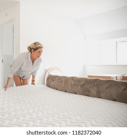 Mature woman is moving in to her new home. She is placing her mattress on her bed.