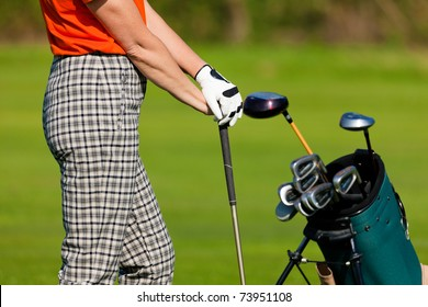 Mature Woman - only torso to be seen - with golf bag playing golf on a golf course