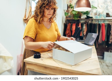 Mature woman packing a box for online order delivery. Fashion store owner preparing a package for shipment.