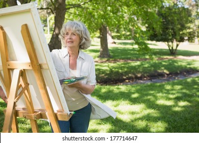 Mature woman painting on canvas in the park