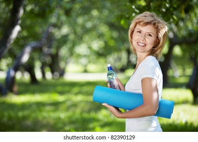 Mature woman in a park with a bottle and gym mat
