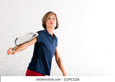 Mature woman playing squash as racket sport in gym, it might be a competition