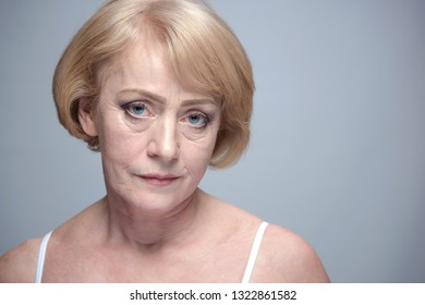 mature woman portrait isolated on blue background face skin head and sholders