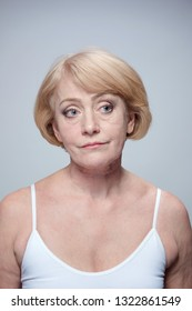 mature woman portrait upset face skin head and sholders isolated on blue
