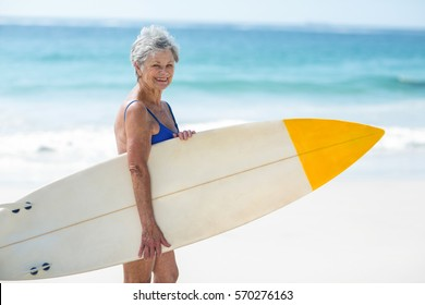 Mature woman posing with a surfboard on the beach