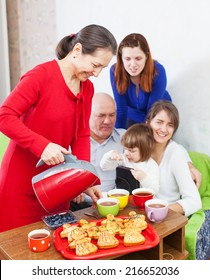 Mature woman pours tea from teapot for family at home