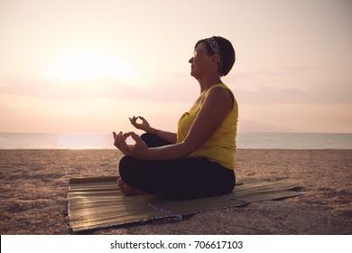 Mature woman practicing yoga at lotus pose, at the sea beach