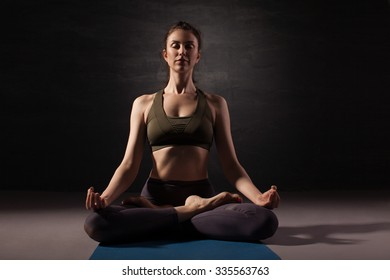 Mature woman practicing yoga on the floor. Studio shoot