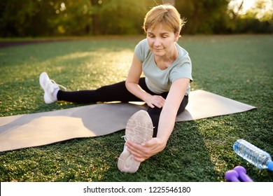 Mature woman practicing yoga outdoor exercise or doing fitness. Healthy lifestyle.