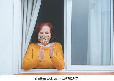 Mature woman with protective mask clapping at the window