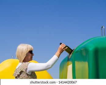 "A mature woman pulling a crystal bottle in a green bin for recycling glass with the spanish text ""only glass containers"""