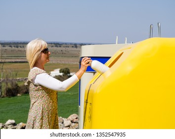 A mature woman pulling a plastic bottle in a yellow bin for recycling plastic