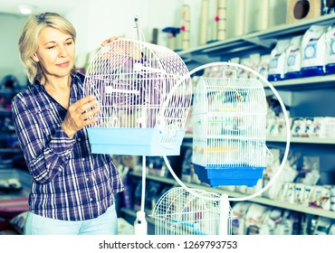 mature woman purchasing bird cage in petshop