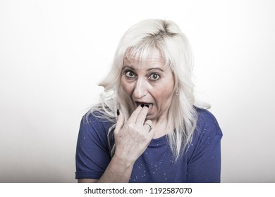 mature woman puts her fingers into her mouth gesturing she will puke due to stomach problems