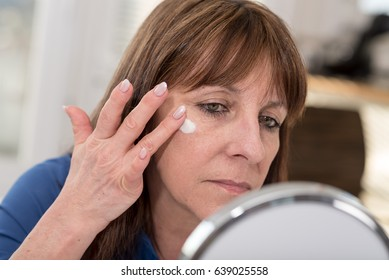 Mature woman putting anti-age cream on her face