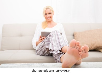 A mature woman in Pyjamas with a Tablet PC on the Sofa.