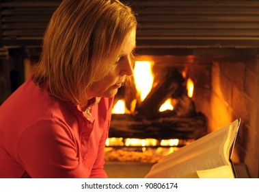 A Mature Woman Reading A Book By Firelight On A Winters Evening At Home