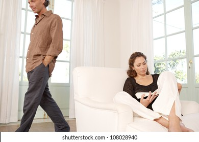 Mature woman reading a book at home while man is walking by.