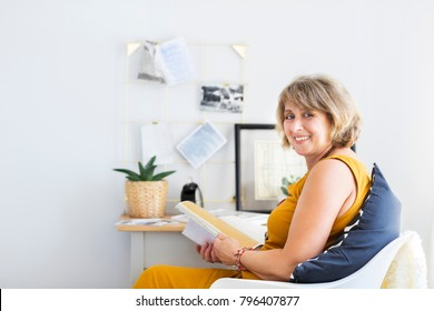 Mature woman reading book in the living room