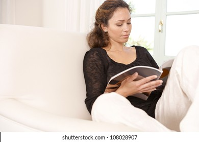 Mature woman reading a magazine while sitting on a white armchair at home.