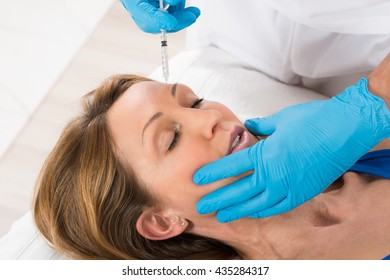 Mature Woman Receiving Cosmetic Injection With Syringe In Beauty Clinic