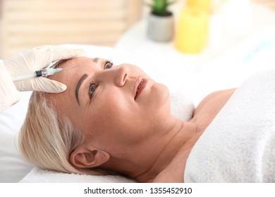 Mature woman receiving filler injection in beauty salon