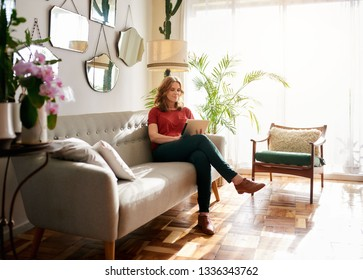 Mature woman relaxing alone on a sofa in her sunny apartment browsing the internet with a digital tablet