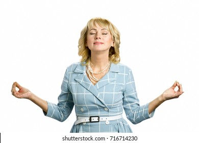Mature woman relaxing, meditating in zen mode. Peaceful white-skin womam meditating on white background. Concept of emotional stress.
