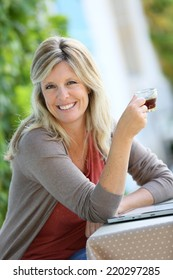 Mature woman relaxing with tablet and coffee in garden