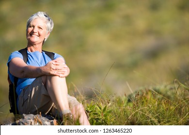 Mature woman resting on hiking along mountain trail at camera