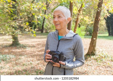 Mature Woman with retro camera ready for taking photo in forest.