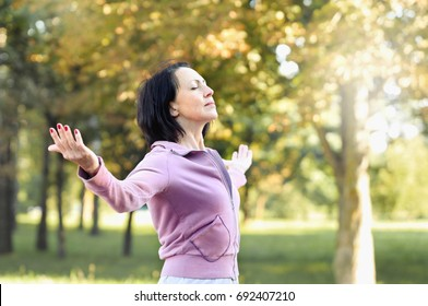 Mature woman runner taking a rest after running in the park. She turn face to sun and hands up.
