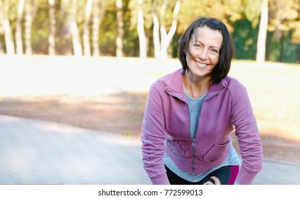Mature woman runner taking a rest after running in the park. Healthy lifestyle concept