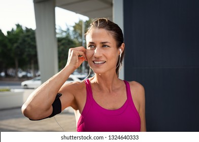 Mature woman runner wearing armband and listening to music on earphones. Fit sportswoman taking a break from outdoors training and looking away. Portrait of smiling woman running on city street.
